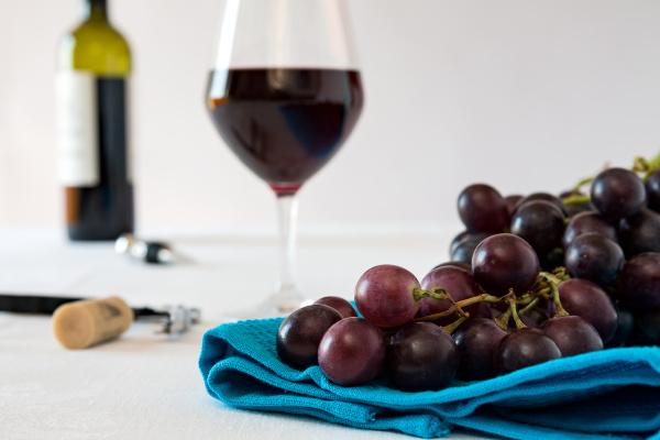zblizenie peczki czerwonych winogron i kieliszek