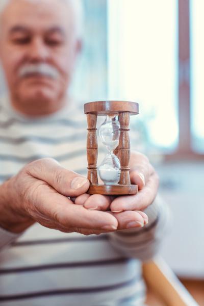 starszy mezczyzna trzymajacy klepsydre w domu