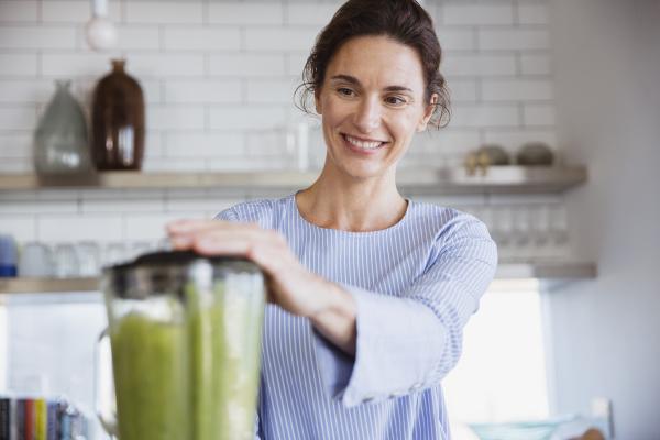 usmiechnieta kobieta robi zdrowy zielony koktajl