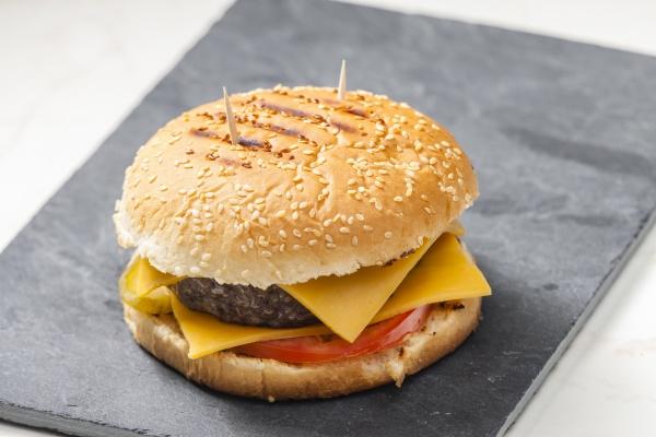 martwa natura cheeseburgera na czarnym talerzu