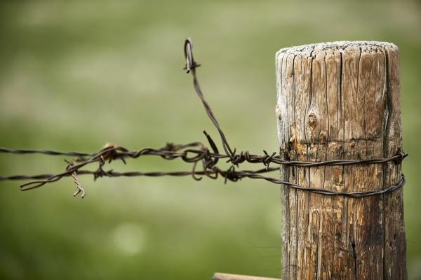 drut kolczasty zwiazany wokol slupka ogrodzenia