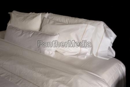 poduszki na lozku hotelowym