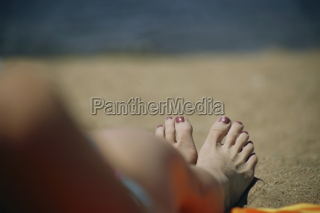 a womans feet on a beach