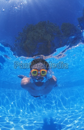 boy with goggles in swimming pool