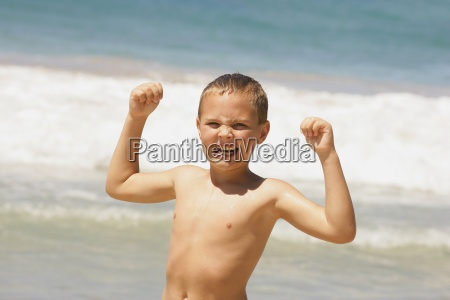 young boy showing off muscles