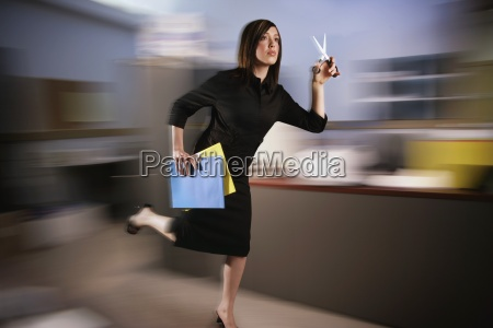 woman runs with scissors through office