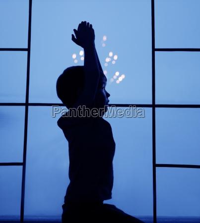 silhouette of small boy in window
