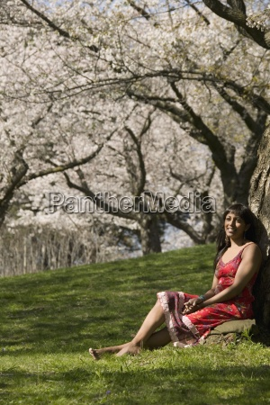 woman relaxing under cherry tree blossoms