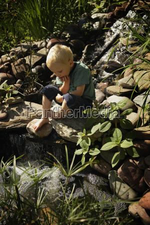 boy sitting by pond