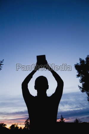 man with bible raised to the