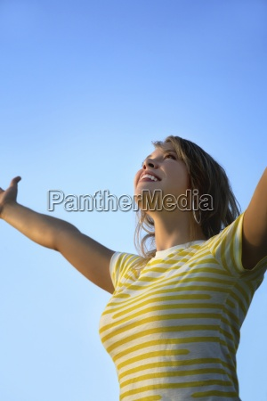 kobieta patrzaca w gore z wyciagnietymi