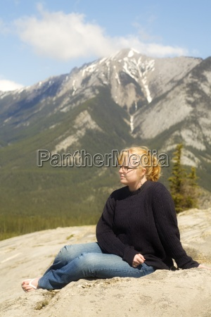 young woman sitting in the mountains
