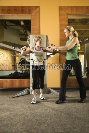 woman helping woman excercise