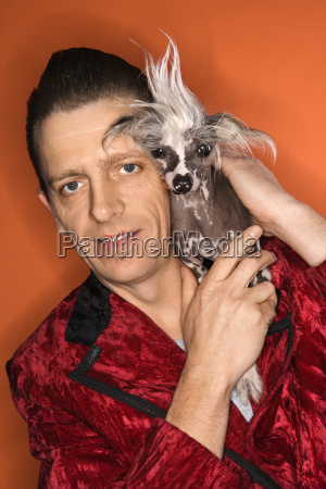 man holding chinese crested dog