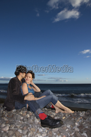 couple snuggling on beach