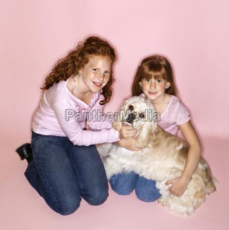 girls holding cocker spaniel dog