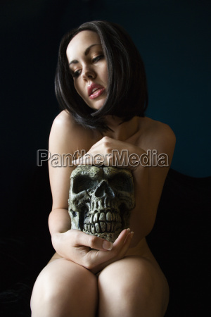 nude woman holding skull