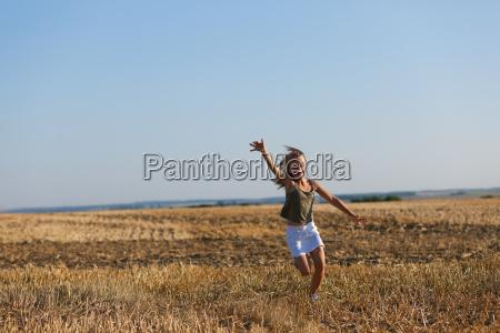 dziewczynka biegnie na polu jesienny