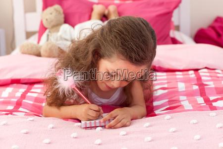 close up dziewczynka pisania na lozku