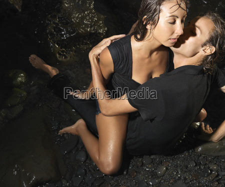 sexy young couple on rocks embracing