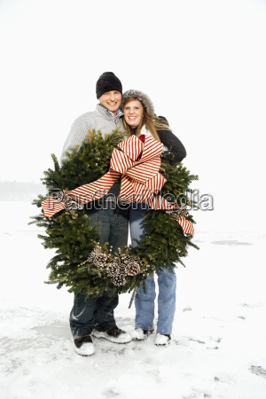 young couple hugging with wreath