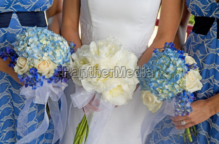bride and two bridesmaids holding bouque
