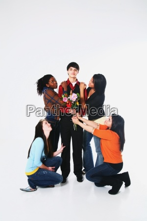 girls surrounding a boy who is