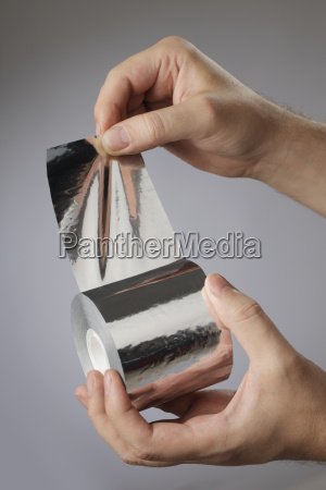 man holding a roll of adhesive