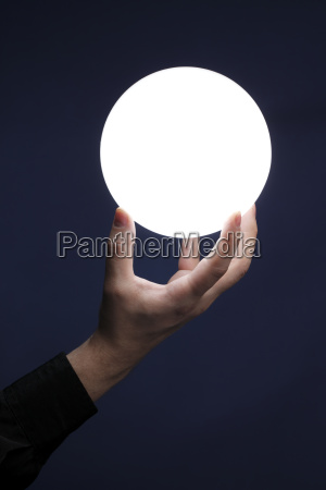 man holding an illuminated sphere