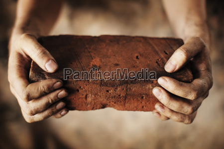 dirty hands holding an old brick