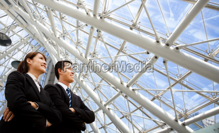two business people stand in modern