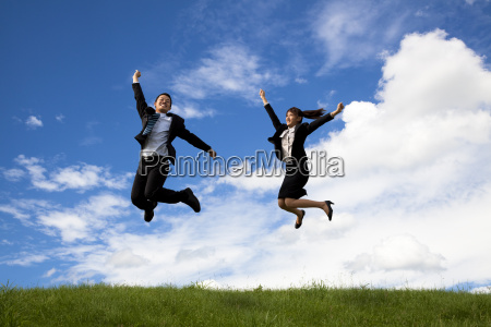 happy businessman and businesswoman jumping on