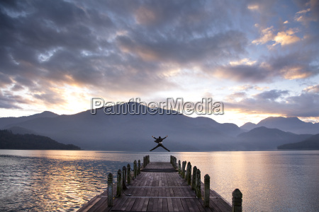 successful businessman jumping on the pier
