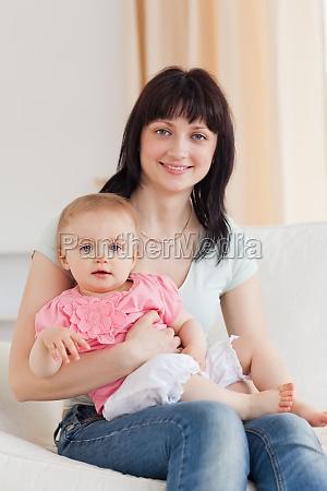 urocza kobieta trzymajac dziecko w ramionach