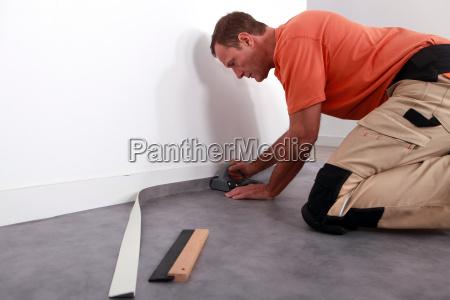 czlowiek ukladanie linoleum na planszy