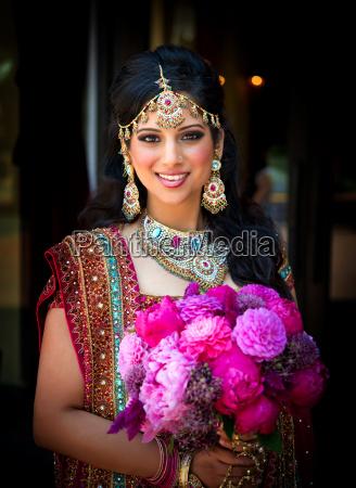 usmiechniety indyjski panna mloda z bukietem