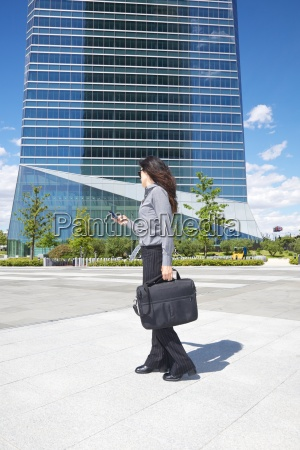 businesswoman with smartphone and briefcase