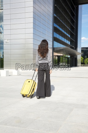 businesswoman with yellow suitcase in front