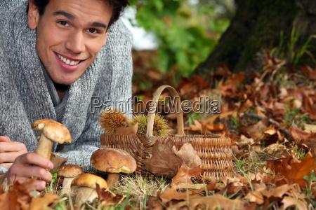 czlowiek zbieranie grzybow i kasztany w
