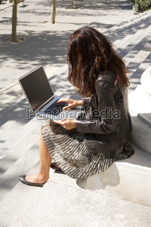 sit businesswoman tapping on portable