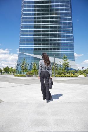 businesswoman walking to skyscraper