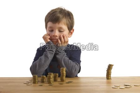 chlopiec patrzy na wieze pieniedzy
