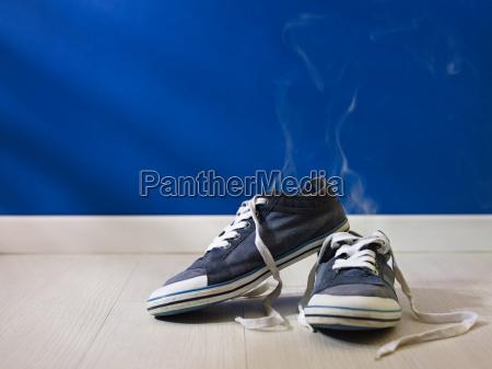 smierdzace buty zuzyte pozostawione na drewnianej