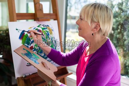 happy starszych kobieta malarstwo dla zabawy