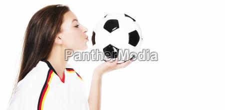 beautiful young woman kissing football