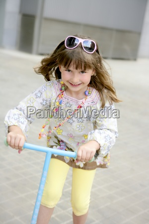brunette little girl with scooter in