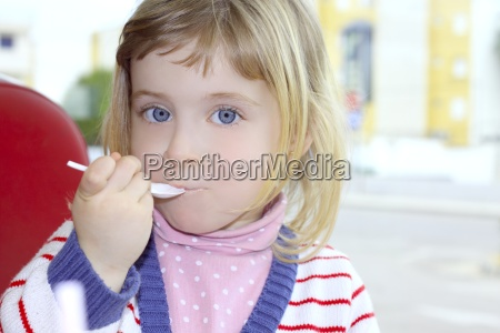 blond little girl portrait eating with
