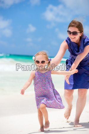 mother and daughter running at beach