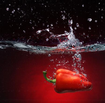 papryka czerwona wpada w tlo wody