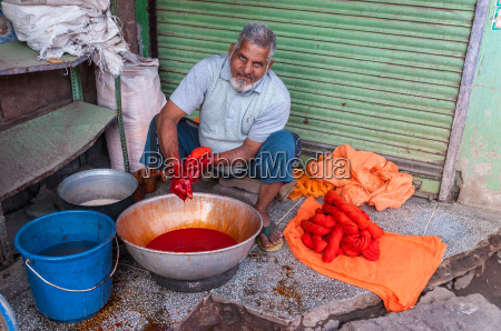 indian man dyed fabrics with red